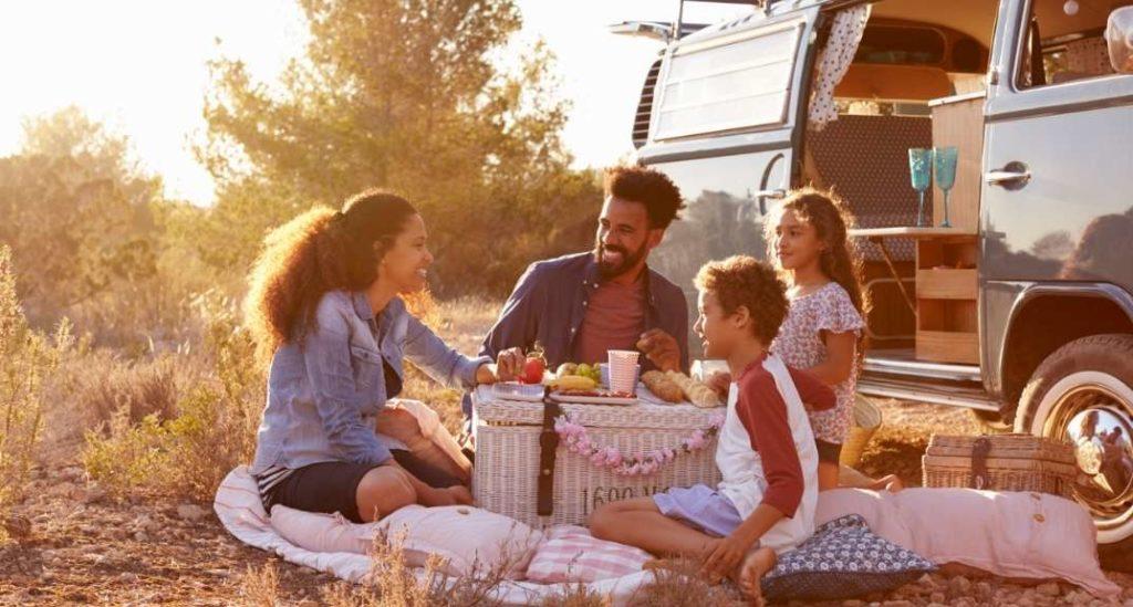 Family having a picnic next to their VW camper van